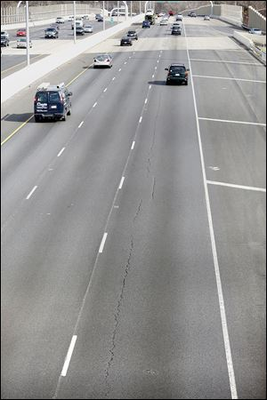 Cracks in the new pavement of eastbound I-475 in West Toledo could have been caused by a design flaw, a problem with the materials that were used, or faulty workmanship, a deputy director of the state transportation district said.