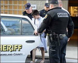 Authorities take attack suspect Alex Hribal, 16, from the magistrate's office after his arraignment in the stabbing of students at Franklin Regional Senior High School in western Pennsylvania.