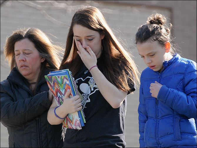 10n5stab A parent escorts distraught students from Franklin Regional Senior High School, where 21 students and a security guard were injured during a Wednesday attack by a 16-year-old with two 8-inch steel knives.