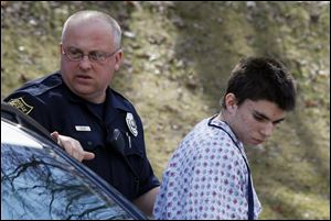 Alex Hribal, the suspect in the multiple stabbings at the Franklin Regional High School in Murrysville, Pa., is escorted by police to a district magistrate to be arraigned Wednesday in Export, Pa.