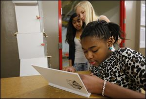 Samoria Russell, a sixth grader at Toledo School of the Arts, draws in a sketch book as fellow sixth graders Imani Allen, back left, and Emma Omlor wait their turn.