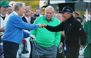 Arnold Palmer, center, watches as Jack Nicklaus, left, and Gary Player touch fists after Palmer hit his ceremonial drive on the first tee during the first round of the Masters golf tournament today in Augusta, Ga.