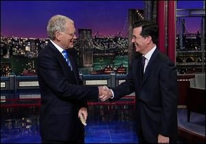 David Letterman shaking hands with fellow talk show host Stephen Colbert of 'The Colbert Report,' during a surprise visit on the 'Late Show with David Letterman,' in 2011 in New York.