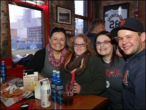 Angela Operacz, of West Toledo, left, Liz Goble, of West Toledo, center left, Amanda LaPoint, of West Toledo, center right, and Mark Blosser, of North Toledo, snagged a window seat at Fricker's to watch the Toledo Mud Hens.