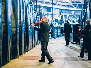 Kirk Toth, concertmaster, warms up backstage.