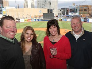Greg and Amy Dunn, left, attended the Toledo Mud Hens' opening day game with Maria Jadwisiak, center right, and Steve Taylor, in The Blade's suite.