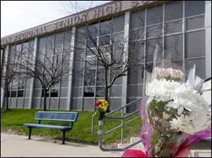 A bouquet of flowers is taped to a stairway rail near the closed entrance to Franklin Regional High School near Pittsburgh, Thursday in Murrysville, Pa.