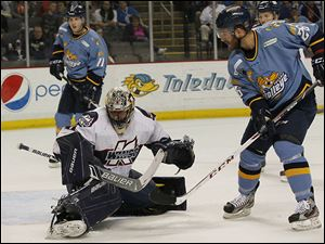 Kalamazoo's Jordan Binnington stops Toledo's Jesse Messier  while the Walleye's Brett Perlini looks on. The Wings' goaltender finished with 30 saves.