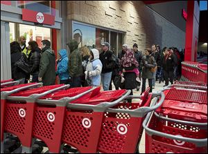Shoppers enter a Target store in Dartmouth, N.S., on Black Friday last year. Since its incursion into Canada in 2013, Target's troubles have included difficulties keeping the shelves stocked and weak sales, resulting in nearly a $1 billion loss for the year.