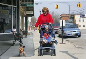 Anita Friend takes a stroll with her grandson Benton Rogge, 2, and her dog Lucy in downtown Antwerp.