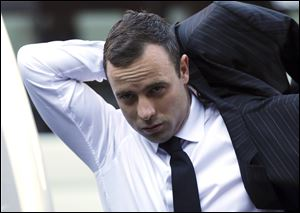 Oscar Pistorius puts on his jacket as he arrives at the high court in Pretoria, South Africa, today.