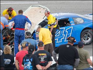 Donny Reuvers (41) looks at his wrecked car after hitting the wall during the 7Up 150 at Toledo Speedway.
