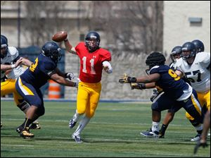 A.J. Bolden and #95, Orion Jones converge on quarterback Logan Woodside as he tries to move the white team.