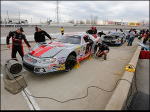 Driver Nathan Haseleu (87) ,left, walks around his car during the break halfway through the 7Up 150 at Toledo Speedway,