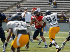 QB Phillip Ely is rushed by #92, Daniel Davis. Behind the QB is head coach Matt Campbell.