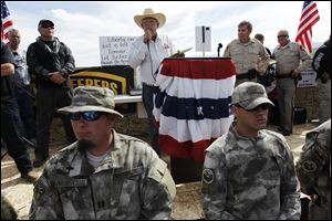 Rancher Cliven Bundy, middle, addresses his supporters along side Clark County Sheriff Doug Gillespie, right, on April 12, 2014. Bundy informed the public that the BLM has agreed to cease the roundup of his family's cattle.