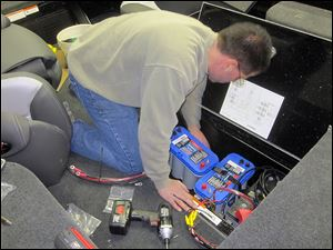 Tom Vatalaro of Vic's Sports Center in Kent, Ohio, installs batteries in the boat of Toledo pro