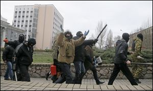Masked pro-Russian activists march after leaving a regional prosecutor's office today in Donetsk, Ukraine.