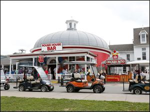 Golf carts along Delaware in front of the Round House Bar.