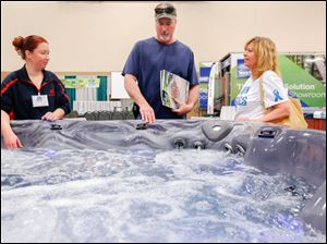 Julie Newell, left, of Preferred Pools and Spas shows Joe Seifert, center, and Sandy Seifert of Findlay a spa.
