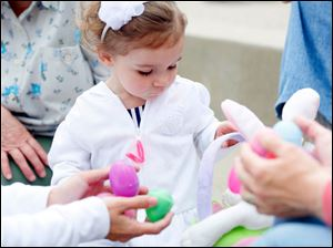 Mackenzie Forrester, 1, of Pemberville looks through the eggs she found for prizes.