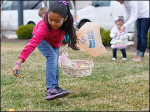 Sofia Gutierrez, 7, of Toledo finds eggs near the clock tower and Hilton Garden Inn in Levis Commons.
