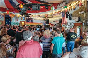 Singer-songwriter Ray Fogg  opens the season in Put-in-Bay, Ohio, as the Round House Bar holds its annual 'whiskey light' celebration.  'All the friends of this harbor will reunite, look for the whiskey light,' he sang.