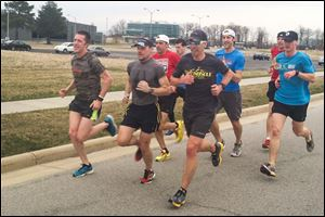 Jon DeWitt, left,  J.P. Miller, and Tim Alderson lead a group of runners at Levis Commons in Perrysburg during a training run Thursday. The three men and Second Sole owner Matt Folk, wearing the red shirt, will be running in the Boston Marathon next week.