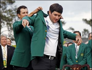 Defending Masters champion Adam Scott helps Bubba Watson on with the traditional green jacket given to winners of the tournament. Watson also won the tournament in 2012.