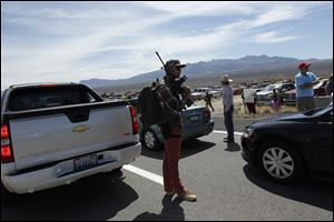 Tyler Lewis, from St. George, Utah, stands in the middle of north bound I-15 with his gun near Bunkerville, Nev. while gathering with other supporters of the Bundy family.