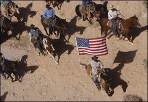 The Bundy family and their supporters fly the American flag as their cattle were released by the Bureau of Land Management back onto public land outside of Bunkerville, Nev.