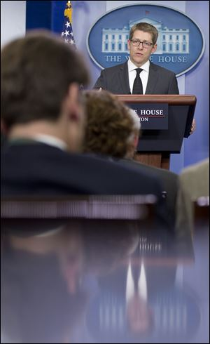 White House press secretary Jay Carney is reflected in a counter as he speaks during the daily news briefing today at the White House in Washington.