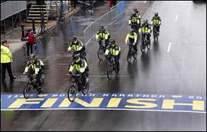 Police on bikes cycle across the Boston Marathon finish line prior to a remembrance ceremony.