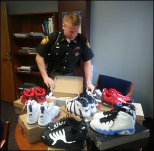aInspector Bill Holland from the Summit County Sheriff's Department delivered 48 pairs of shoes seized in a drug bust to excited workers at Summit County Children Services in Akron.