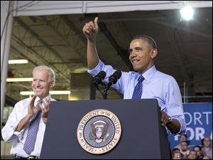 Vice President Joe Biden applauds, at left, as President Barack Obama gives the thumbs up as he talks about his job training program in Oakdale.