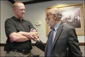Tim Bork, left, speaks with his attorney Alan Konop, right, in the foyer of the Fulton County Court Eastern District, on September 11, 2013.  Mr. Konop is representing  Mr. Bork in court over charges stemming from his refusal to register his dog