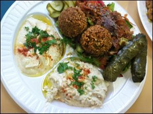 The Lazeez plate includes two pieces of falafal, two veggie grape leaves, hummus, baba gannouch, pita bread and a side of soup or salad.