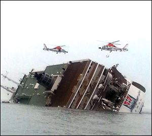 South Korean rescue helicopters fly over a South Korean passenger ship, trying to rescue passengers from the ship in water today off the southern coast in South Korea.