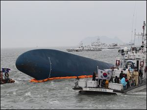 South Korean Coast Guard officers try to rescue missing passengers from a sunken ferry in the water off the southern coast near Jindo, South Korea, Thursday0
