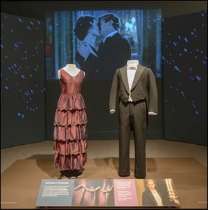 At the Winterthur Museum Costumes of Downton Abbey exhibition, fans of the British TV show can ogle such finery as the red dress and dapper suit worn by characters Mary and Matthew for their Season 2 engagement scene, shown on the screen in the background.
