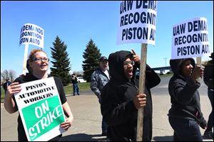 Piston Automotive employees, from left, Amanda Dickerson, Rae-Lyn Fobbs, and Sonya Hill picket in support of forming a union in North Toledo. About 50 employees, other union members, and supporters turned out to picket Thursday. The dispute ended about eight hours after it started.