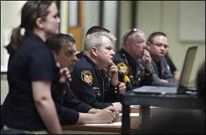 Deputy Jason Langlois, center, and other officers listen to Megan Anello, left, an agent with the Bureau of Criminal Identification and Investigation, during a training session at the sheriff's office.