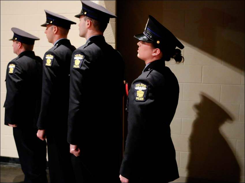 Toledo Police Academy graduates from left to right Duane Isabell, Brian Jackson, Zachary Jennings, and Kilee Keplinger wait to receive their badges during the 61st Toledo Police Academy Graduation.