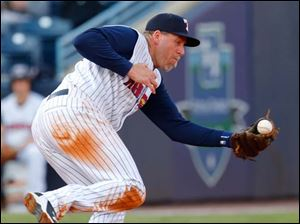Mud Hens player Mike Hessman bobbles a ball hit by Columbus player Roberto Perez (10) during the third inning.