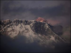 The last light of the day sets on Mount Everest as it rises behind Mount Nuptse as seen from Tengboche, in the Himalaya's Khumbu region, Nepal in October, 2011.