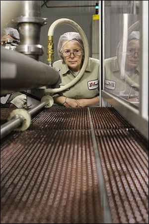 Debra Gonzalez, who has worked at Blommer Chocolate for 17 years, inspects chocolate chips as they are dropped onto a conveyor belt and sent through a cooling chamber.
