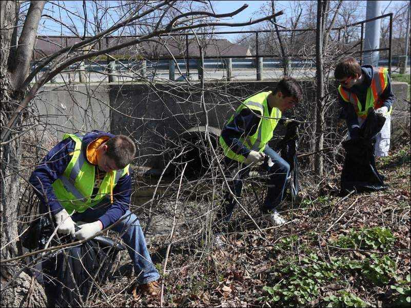 University of Toledo students Clint Hardman, left, Zach Guenin, center, and Robert Cagle, right, collect refuse from the stream bank near Sandusky Street during the kick-off for the Great American Cleanup near Three Meadows Park in Perrysburg.