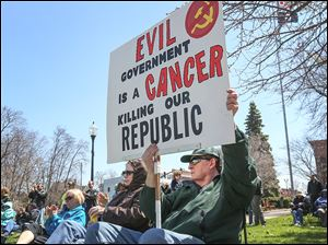Bob Spudie of Perrysburg holds his sign up as he joins other area residents at the Northwest Ohio Tax Day Tea Party Rally at Hood Park in Perrysburg. About 50 people, including several local politicians and candidates, were on hand to talk about politics.