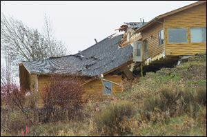 A house breaks apart as a slow-moving landslide in Jackson, Wyo. advances downhill Friday. The slide has cut off access to a 60-person neighborhood.