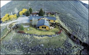 This aerial image provided by Tributary Environmental shows a home damaged by a landslide Friday in Jackson, Wyo.